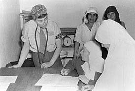 Scene showing American Friends Service Committee midwives and refugee women helpers in a clinic at Khan Yunis in Southern Palestine.