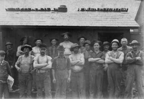 Group photograph of workers at the Shenango Furnace.  Front row, left to right:  Unknown (man with newspaper), Redmond, unknown, Childs, unknown, Ernest Rapp, Armour, Tim Moore