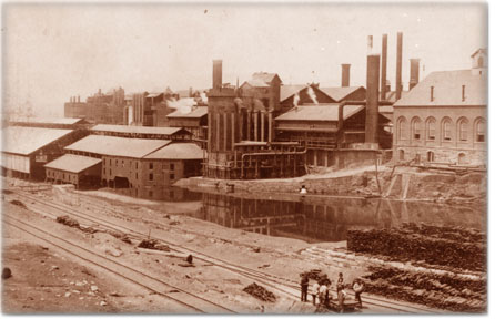 Part of the production facilities at the Lackawanna Iron and Steel Company, with workers standing along the tracks.