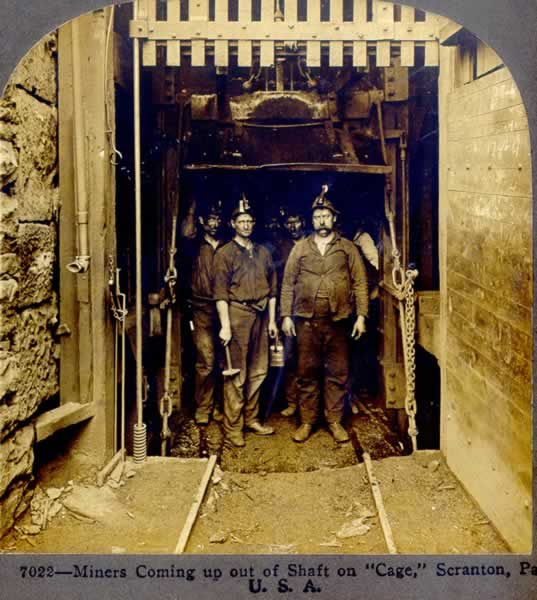 Miners are coming out of the elevator that takes them down into the shaft mine opening.