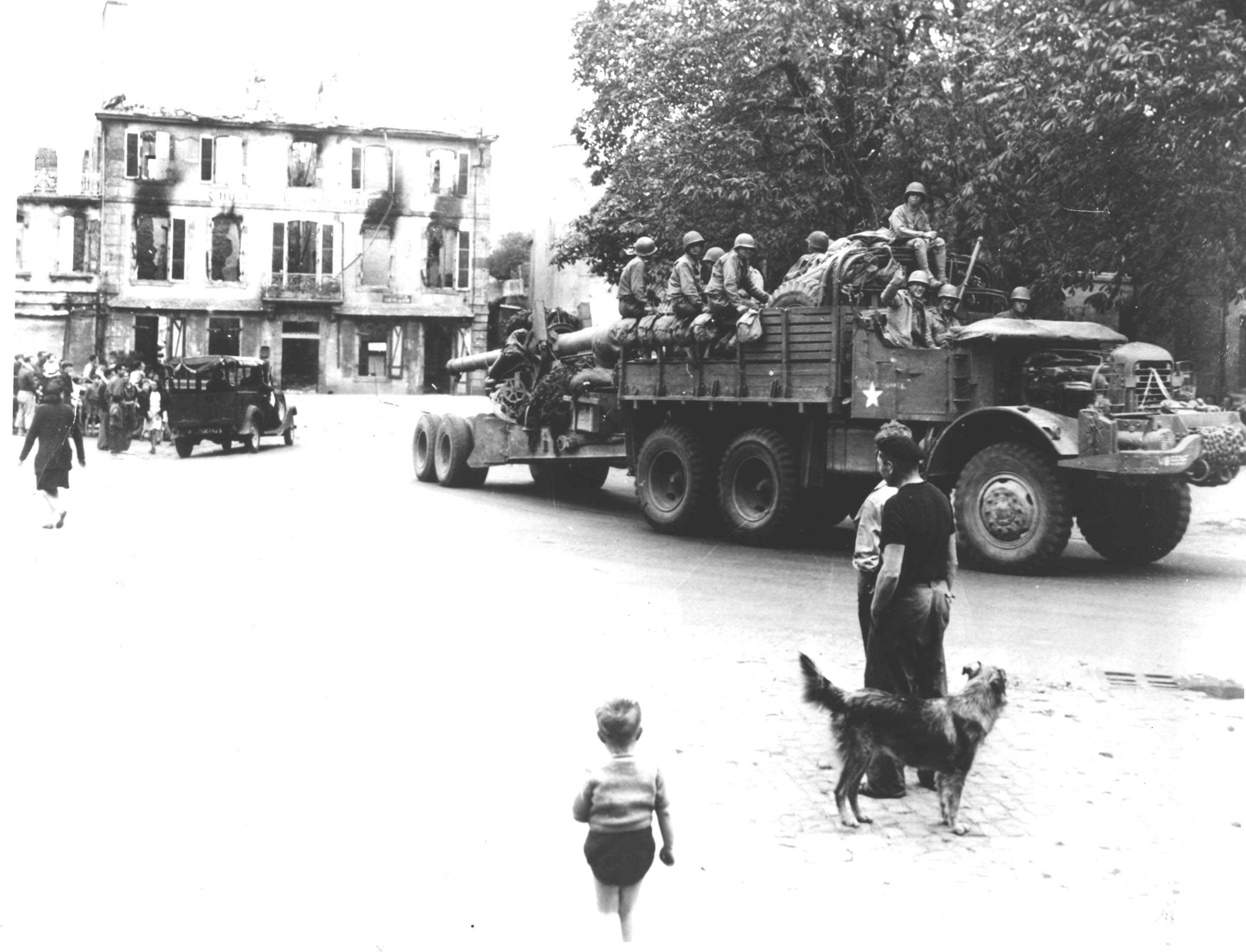 Image of truck with soldiers riding in the back making its way through